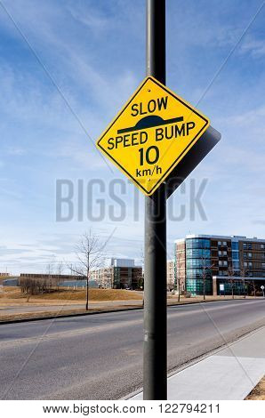 A slow down traffic sign in a residential area indicating a speed bump and a 10 km per hour driving speed.