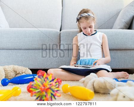 It's time to clean up your toys! Little girl playing with tablet pc don't want to do the cleaning.