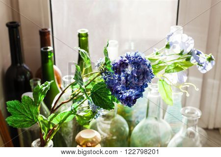still life - textile artificial flower and old bottles covered with dust on window sill illuminated by sunlight