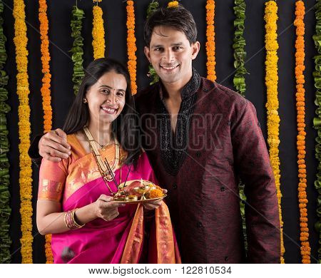 Portrait of Maharashtrian couple holding a puja thali, indian couple holding puja thali or pooja thali, indian couple celebrating diwali, laxmi pujan, asian couple and puja thali, couple doing prayer