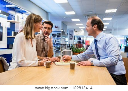Salesman asking young couple to sign the sale receipt in electronics store