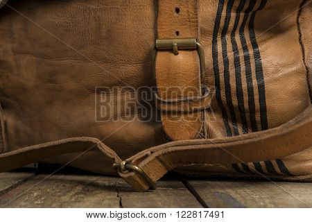 Strap fastened on to metal buckle of brown leather bag with black thin stripes on the side. poster