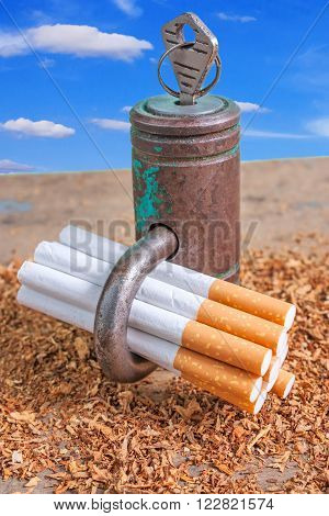 Antismoking background with broken cigarettes and a padlock on blue sky background vertical