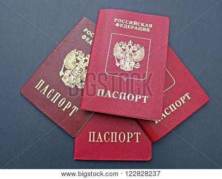 Several passports of a citizen of Russian Federation on black background. The inscriptions in Russian