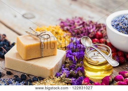 Bars of homemade soaps, honey or oil, heaps of healing herbs and mortar of lavender. Selective focus.
