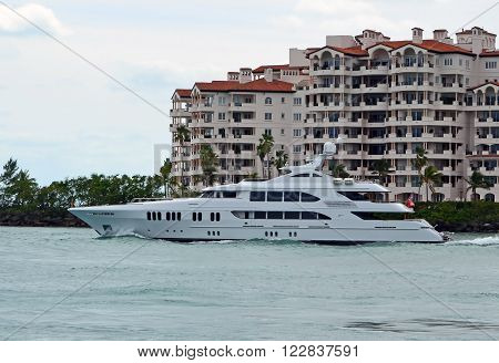 Luxurious motor yacht on it's way out to sea cruising by luxury condominiums on an island off Miami Beach,Florida