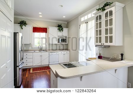 Modern residential kitchen with white cabinets and maple floors