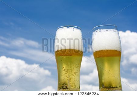 Two glasses of frothy beer under blue sky
