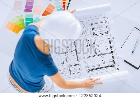 architecture, interior design and renovation concept -  woman in helmet working with color samples and blueprint