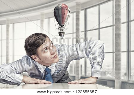 Big businessman peeping from under table