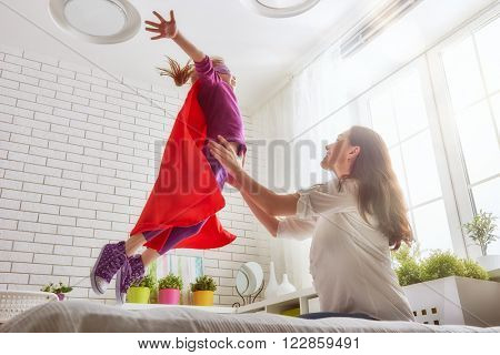 Mother and her child girl playing together. Girl in an Superhero's costume. The child having fun and jumping on the bed.