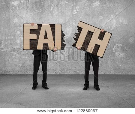 Men holding two cracked FAITH word wooden boards with concrete wall and floor indoor background.