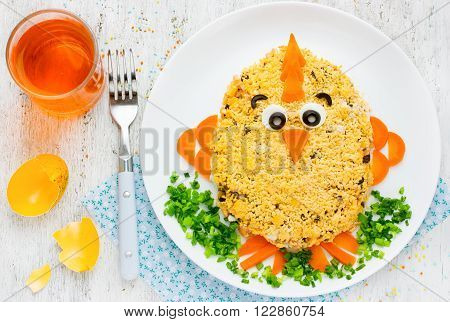 Easter cute salad. Creative food art idea on Easter meal party for children. Thematic Easter snack shaped funny chick decorated egg yolk and vegetables