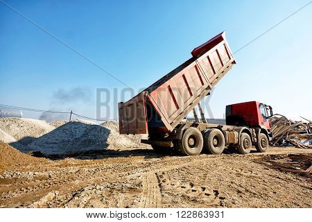 Dumper truck unloading soil or sand at construction site at blue sky background