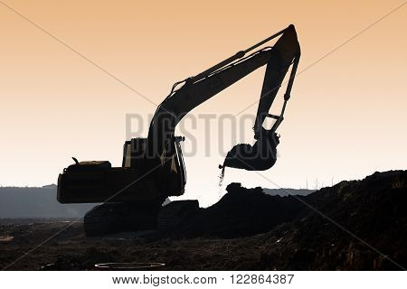 Excavator loader machine during earthmoving works outdoors at construction site silhouette