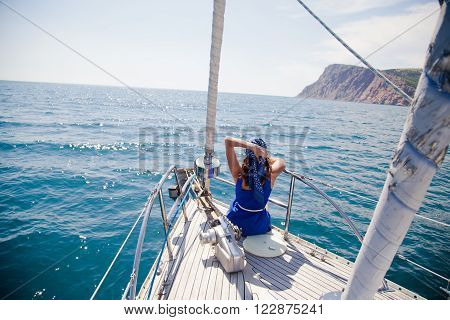 a young girl on the nose of the white yacht in a nautical theme. blue jacket, blue scarf and sun glasses.  in the open sea the ocean