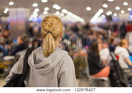 Young blond caucsian woman waiting on airport terminal full of passenegers waiting to depart.