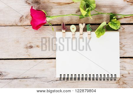 Red rose flower vintage book and love text on the wooden valentine's day for background