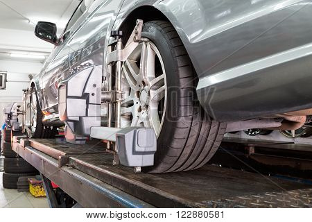 Closeup of tire clamped with aligner undergoing auto wheel alignment in garage poster