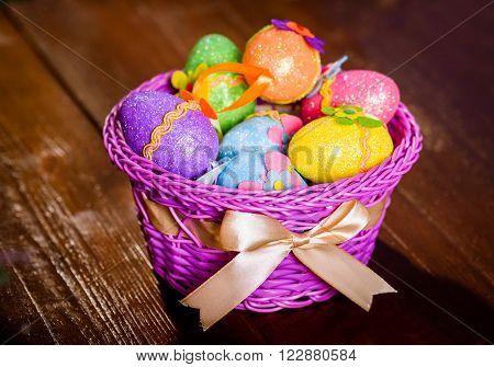 easter eggs in violett basket on wooden background