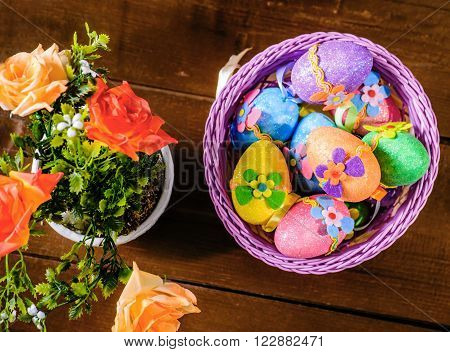 easter eggs in violett basket and rose flowers in a pot on wooden table. Top view.