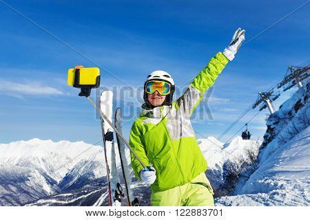 Woman taking a selfie with stick and lifted hand over the mountain and cablecar ski lift with cabins