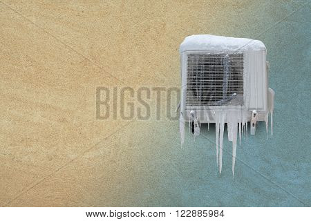 Frozen air conditioner with icicles. Heating and cooling concept. Vintage sand stone wall background. Toned photo. copyspace