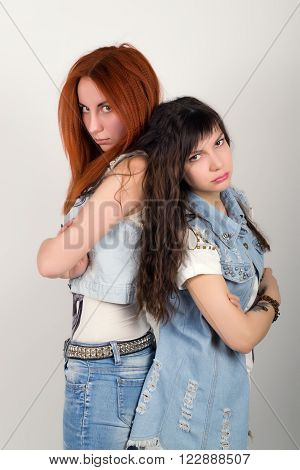 two girlfriends were offended, turned their backs to each other. different emotions. looking away after conflict at home.