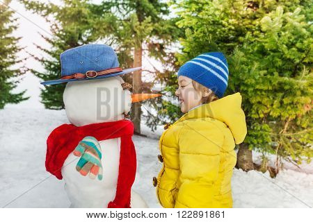 Little boy in yellow coat stand looking on the dressed in hat and scarf snowman he just made