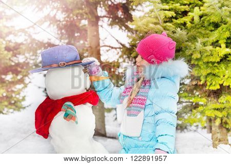 Little girl in blue coat stand looking on the dressed in hat and scarf snowman she just made