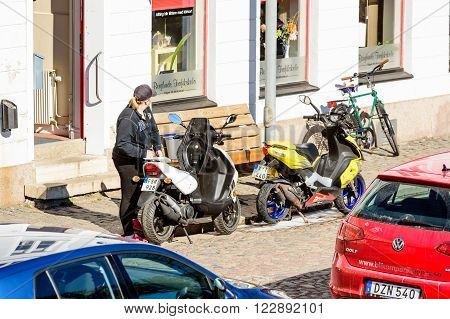 Kalmar Sweden - March 17 2016: A young adult female stand beside a moped outside a driving school. Mopeds saddle is open and the woman looks away into the school. Real people in everyday life.