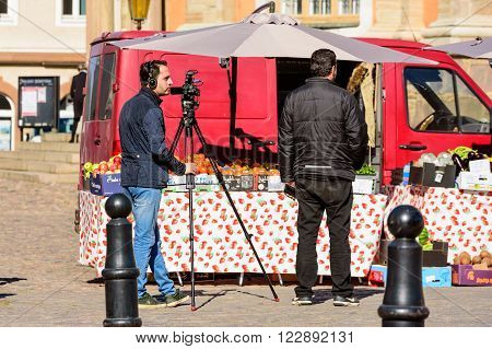 Kalmar Sweden - March 17 2016: Two male persons with a Canon video camera on a tripod waiting to shoot at a fruit vendors place at public market. Red car in background. Everyday life in town.