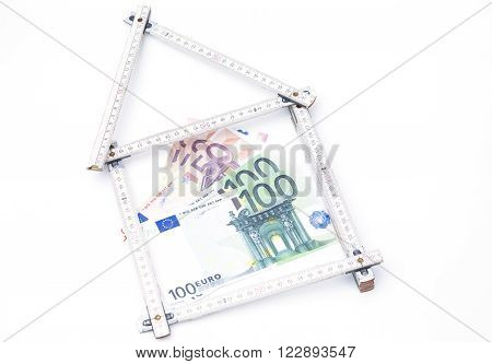 Image shows a folding rule hous with money isolated on white