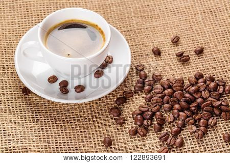 Beautiful White Coffee Cup And Saucer And Coffee Beans On The Background Of Burlap. Dark Background.