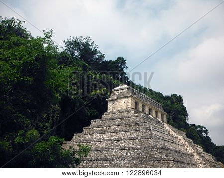 The Mayan Temple of Inscriptions at the Palenque archeological site in Chiapas Mexico backed by dense jungle.