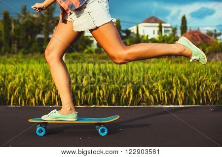 Girl skateboarder legs skateboarding at sunset rice fields
