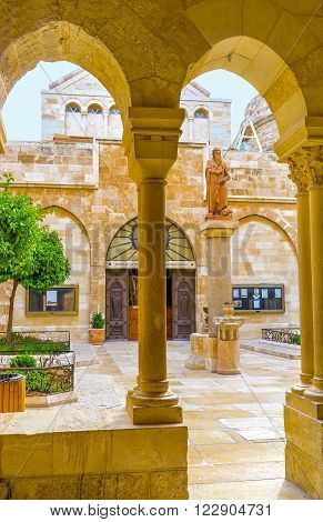 BETHLEHEM PALESTINE - FEBRUARY 18 2016: The statue to the St. Jerome located in the middle of the inner courtyard of the Church of the Nativity on February 18 in Bethlehem.