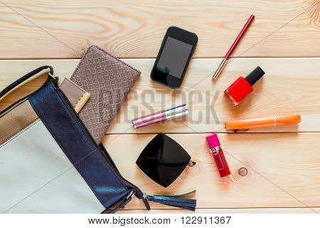 Female Bag And Cosmetics Scattered On The Wooden Floor