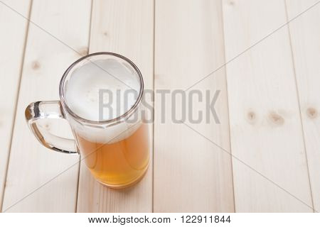 Mug of unfiltered beer on the wooden table. Top down viewpoint.