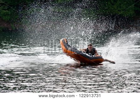 Young man tubing behind a boat on a lake.