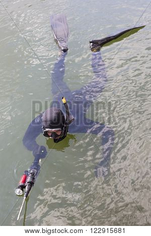 Spearfishing. Underwater hunter dives into the sea.