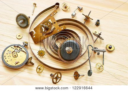 Pile of the old parts of  mechanical clocks on a wooden background