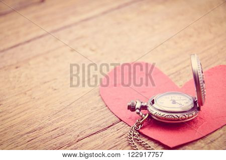 Long necklace antique style pocket watch with a red mulberry paper heart on a wooden surface. A symbol to express someone eternal love on special occasions i.e. Valentines day, Fathers & Mothers Day.