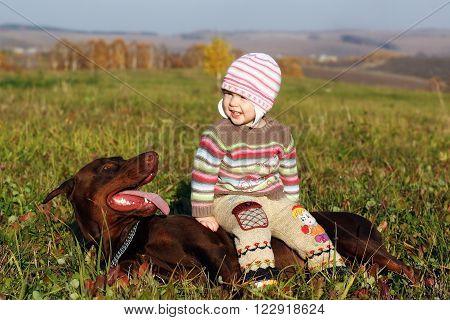 A little girl befriends a large dog Doberman