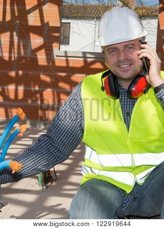 Entrepreneur male on construction site using smartphone