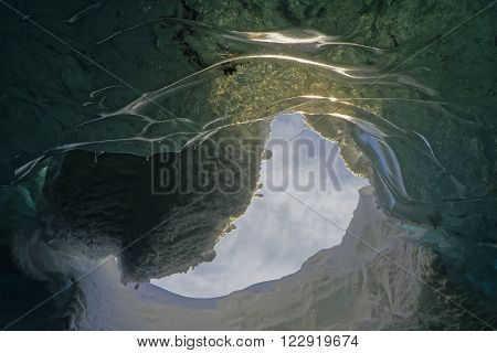 Hole in the glacier Vatnajokul up to the sky