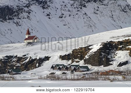 A church on the snowy hill of the town of Vik, Iceland