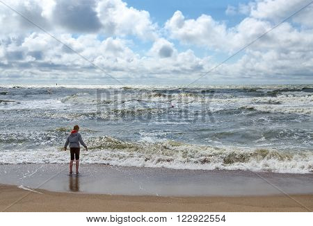 KLAIPEDA LITHUANIA - JULY 11 2015: Unknown boy stands on the shore of the restless Baltic Sea in typical windy cool weather in July