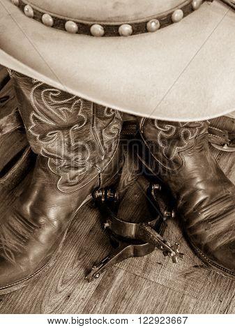 Cowboy hat, cowboy boots and spurs.  Sepia