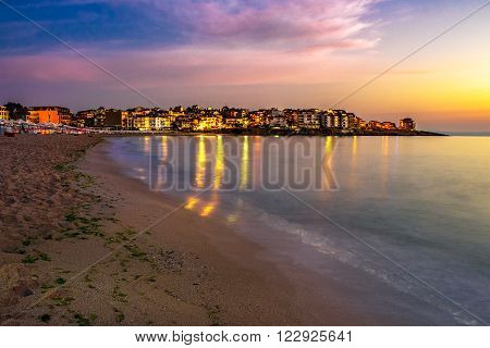 Sea waves at sunrise on empty sandy beach of ancient european resort town Sozopol in summer